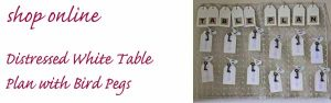 distressed white table plan with bird pegs