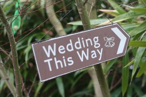 wedding this way brown road sign
