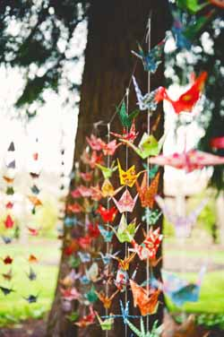 bright coloured paper cranes wedding backdrop outside