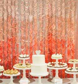 ombre orange paper cranes backdrop behing wedding cake and dessert table