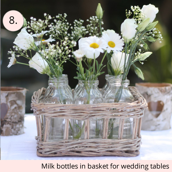 country garden wedding centrepieces milk bottles in a wicker basket - 15 wedding centrepieces for under 15 pounds (budget friendly centrepieces)