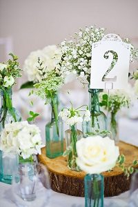 english country garden wedding centrepiece with bottles on wooden tree slice
