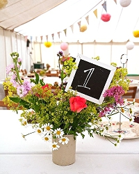 english country garden wedding table decoration idea a simple vase with wild flowers and a blackboard table number
