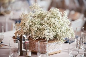 square vase covered in hessian lace with gypsophilia rustic wedding centrepieces