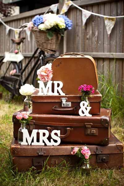 use suitcases at weddings stacked up to display signs and props