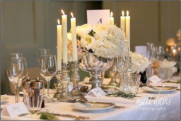 Mercury silver candle sticks around stunning silver footed vases of hydrangeas and roses