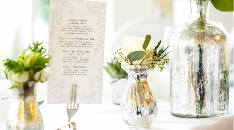Mercury silver vases on wedding tables with cream and grey flowers