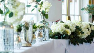 Wedding top table ideas with mercury silver vases and cream roses