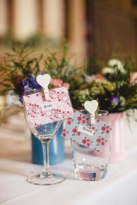 White heart pegs on wine glasses for place names