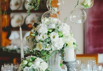 grey urn wedding centrepiece with hanging glass vases and candle holders
