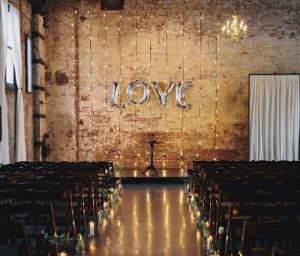 industrial rustic wedding ceremony exposed brickwork candles down the aisle silver love balloons