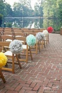 paper pom poms tied to chairs make aisle decorations