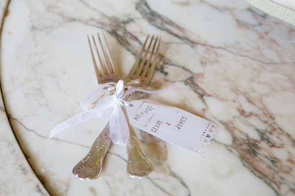 Luggage tag personlaised with the name of the couple tied to the cutlery
