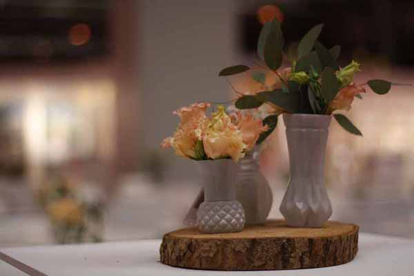 Grouping of white vases wedding centrepiece on tree slice for rustic winter wedding