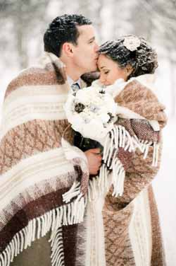 warm and cosy wedding photos bride and groom with blanket