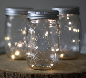 Mason Jar with Fairy Lights on tree slices for centrepieces available from @theweddingomd
