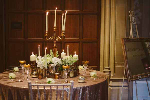 Gold vases for wedding centrepieces around the base of gold candelabra