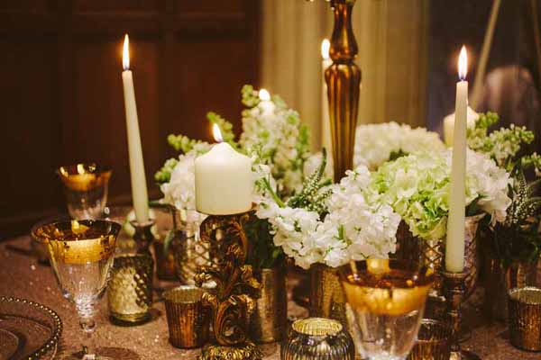 Wedding centrepueces with gold vases and bottles filled with flowers around the base of gold candelabra