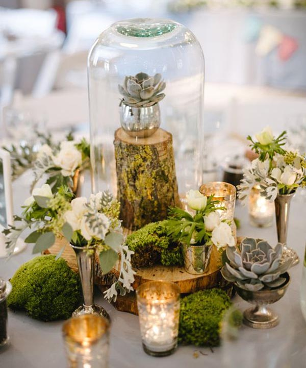 bell jars for wedding centrepieces use different heights and add moss and tree stumps for a rustic look
