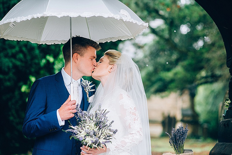 Bride and groom having a lovely day in the rain love the white umbrella