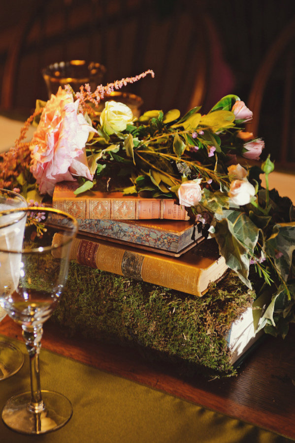 books wedding centrepieces covered in moss