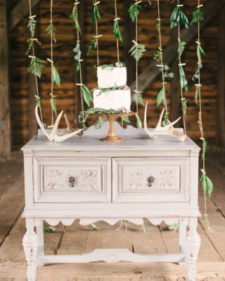foliage pegged on twine makes wedding cake backdrop