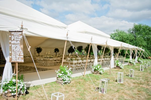 marquee wedding decorations wooden signs lanterns flowers in crates