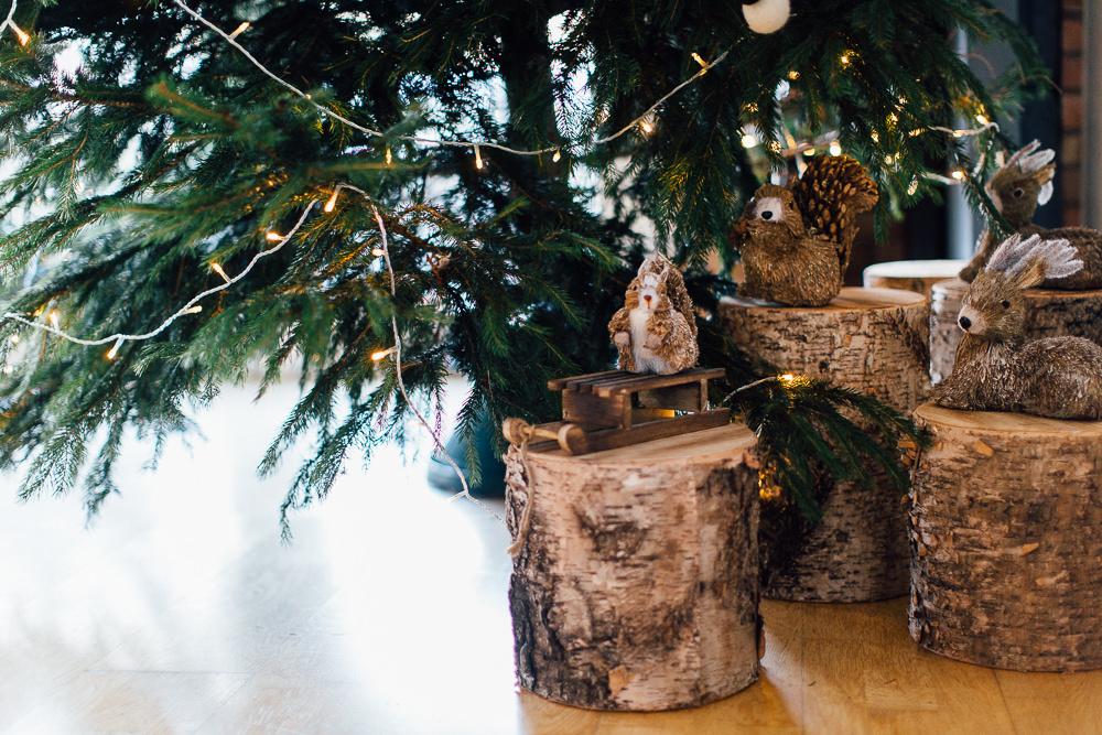 Woodland animals on tree stumps under Christmas tree
