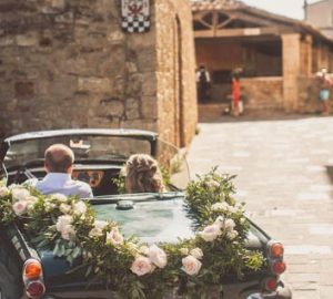 wedding car with floral garland of roses foliage
