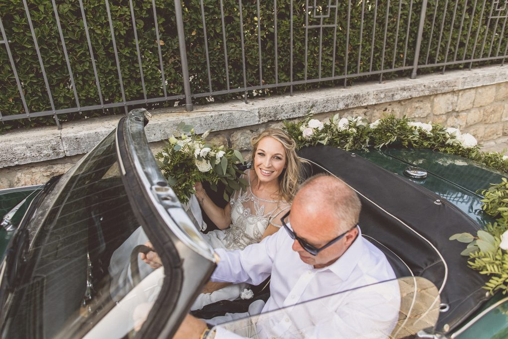 Bride and father of the bride wedding car floral garland Destination wedding Italy Tuscany