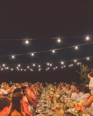 long wedding tables outside with festival lights