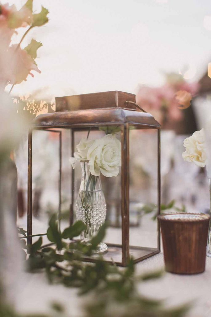 Brass lanterns with small bud vases inside wedding centrepieces