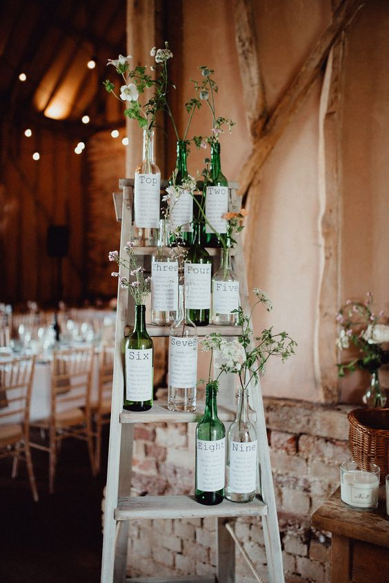 wedding table plans wine bottles with flowers on ladders
