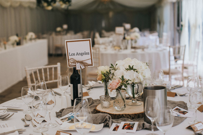 Rustic elegant centrepieces tree stumps with gass vases and grey runner Birtsmorton Court Marquee wedding