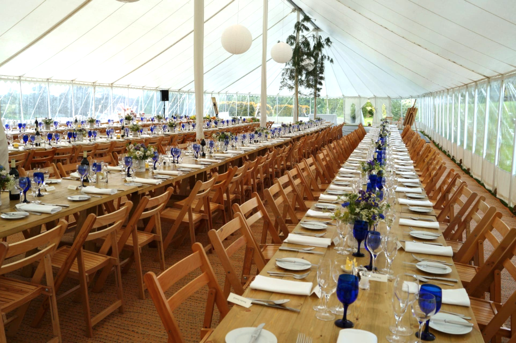 Marquee weddings long wooden tables flowers in small jars Space Intense