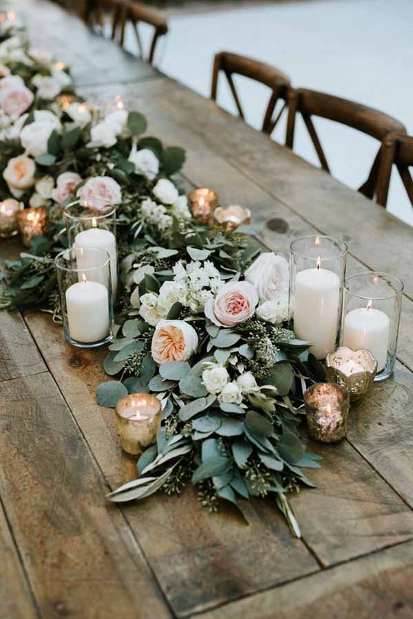barn wedding centrepieces lush floral garlands with cylinder vases lanterns
