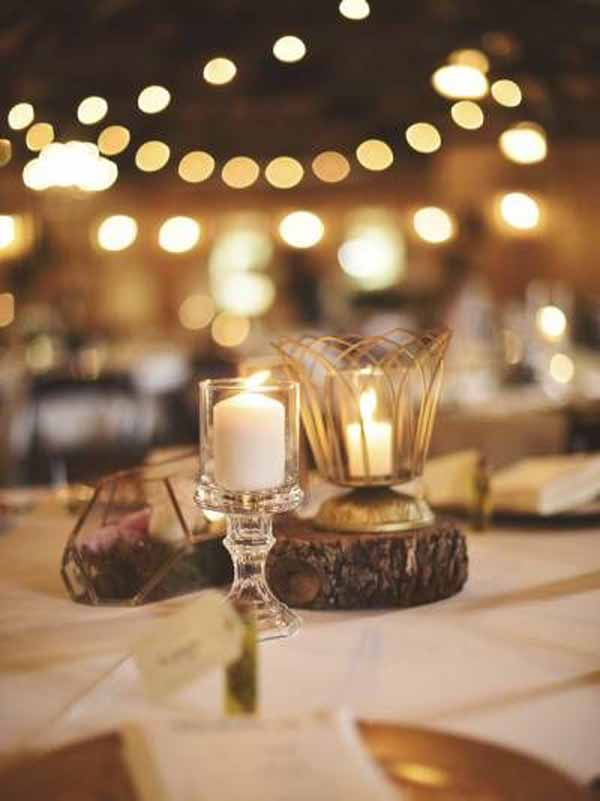 barn wedding centrepieces tree slices with gold lanterns