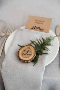 barn wedding place settings wooden tree slices and foliage