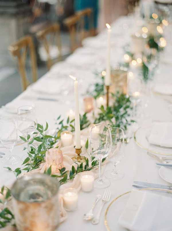barn wedding with delicate loose laid foliage cream table runners and gold candlesticks