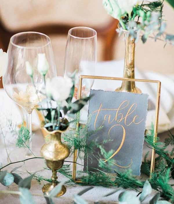 barn wedding with gold table numbers in frames