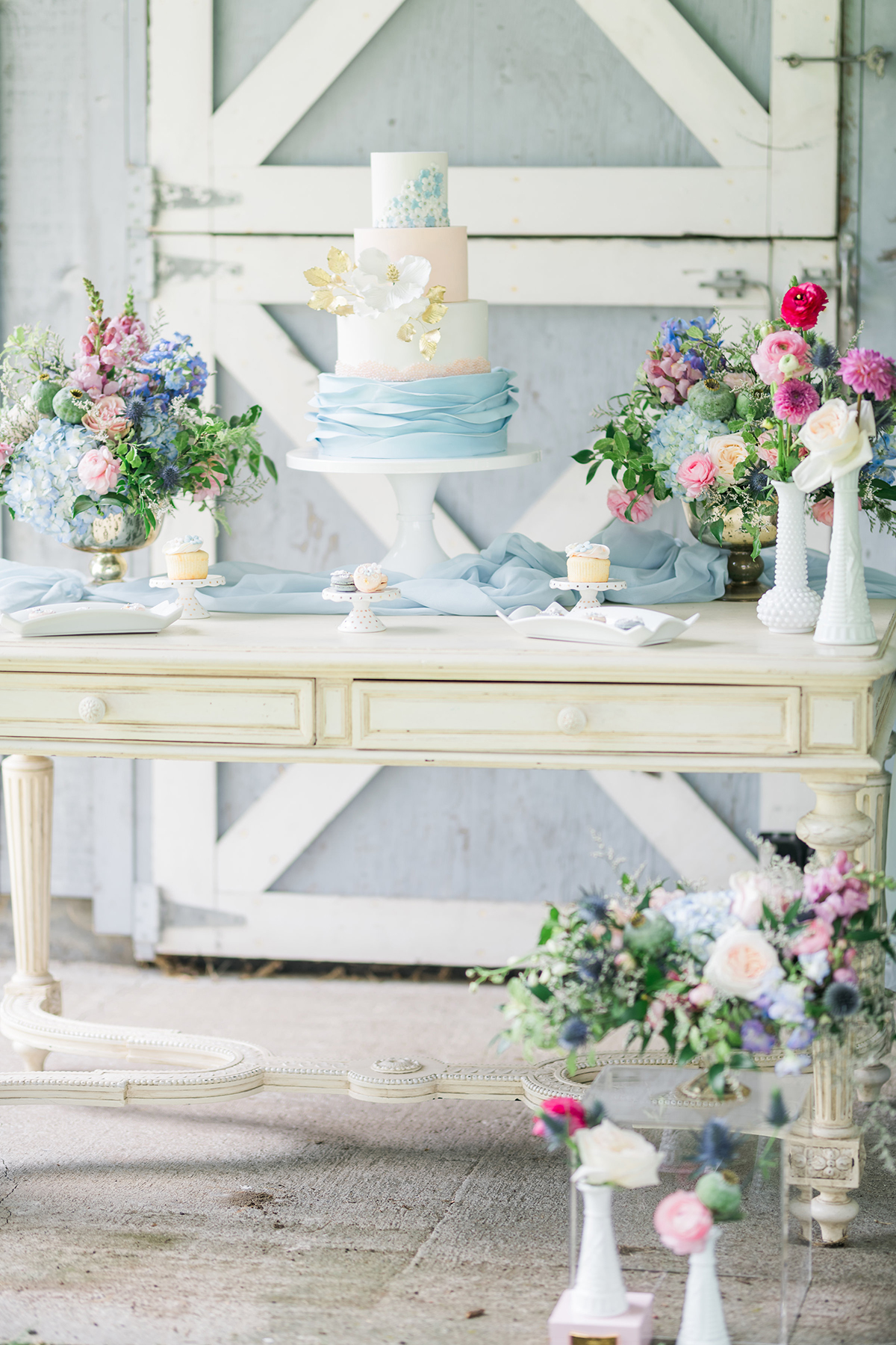 summer barn wedding blue cake table with gold footed bowl wedding flowers centrepieces