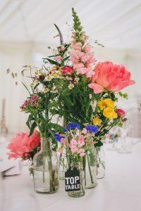 wildflowers in glass bottles wedding centrepieces marquee