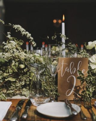 long wedding table garlands brass candlesticks and brown table numbers