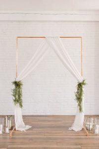 wedding backdrops copper arch drapes and foliage